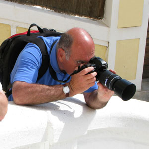 male photography leans on white wall to take a picture with a telephoto lens